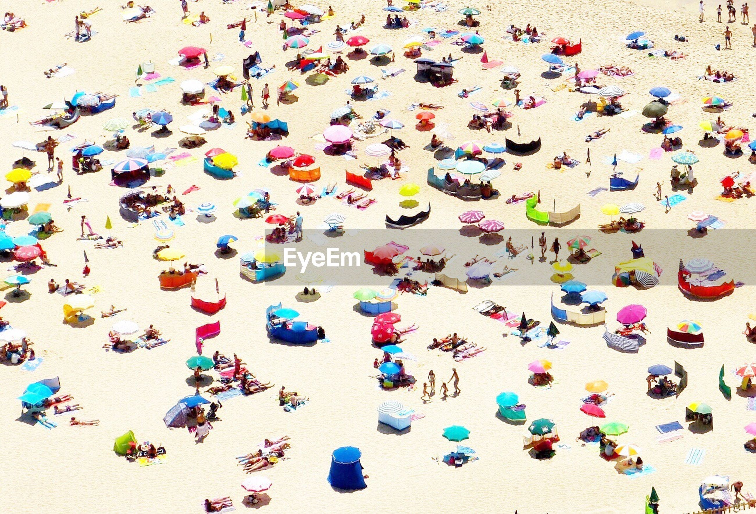 High angle view of people and parasols at beach during sunny day