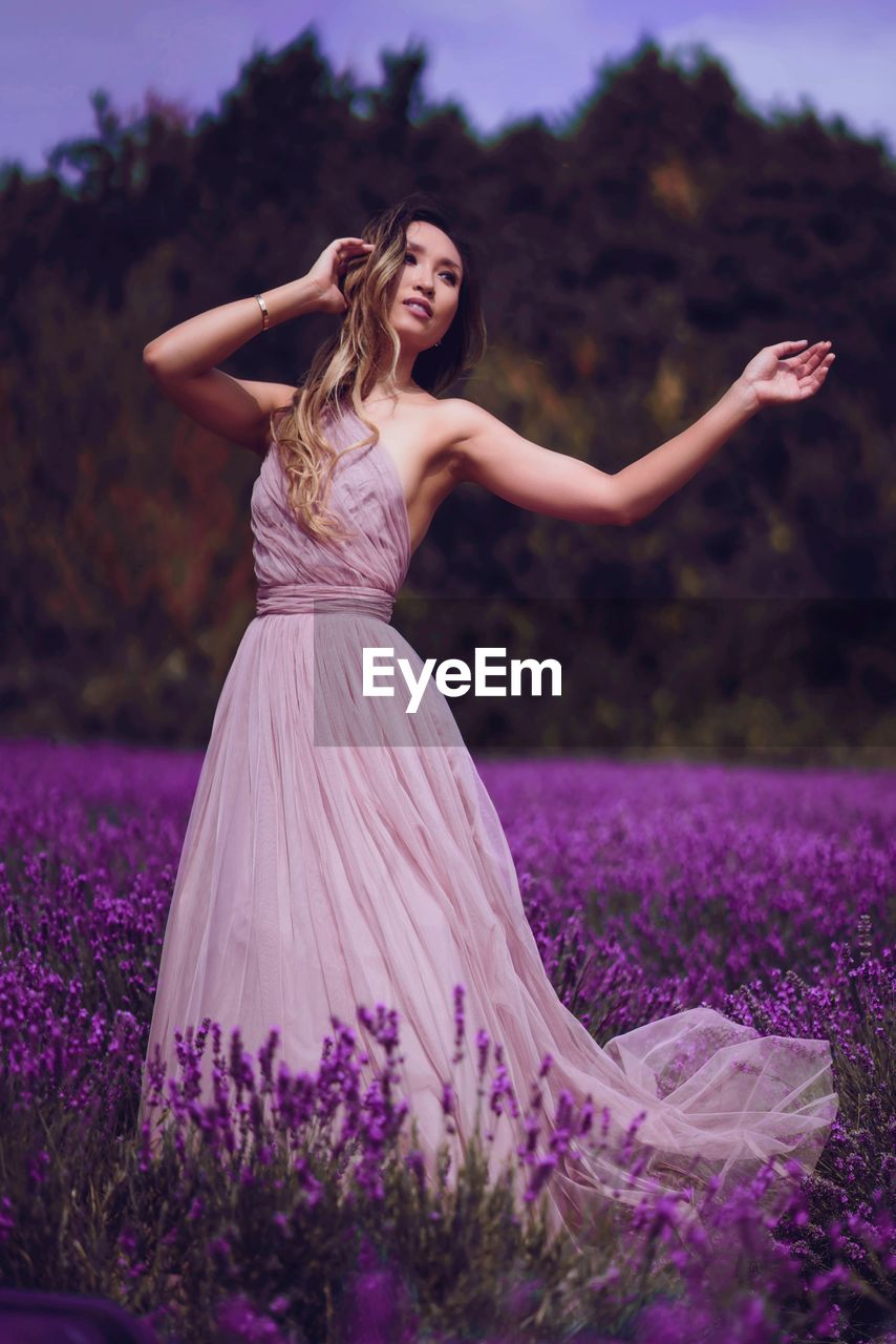 one person, women, young women, young adult, plant, fashion, three quarter length, field, full length, lifestyles, dress, leisure activity, real people, looking at camera, human arm, adult, happiness, smiling, purple, hair, outdoors, hairstyle, beautiful woman
