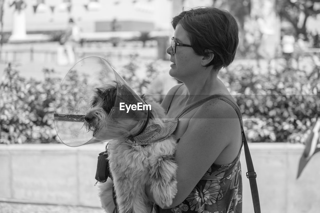 one animal, real people, animal themes, pets, dog, focus on foreground, domestic animals, leisure activity, mammal, side view, one person, casual clothing, outdoors, day, young adult, young women, lifestyles, eyeglasses, nature