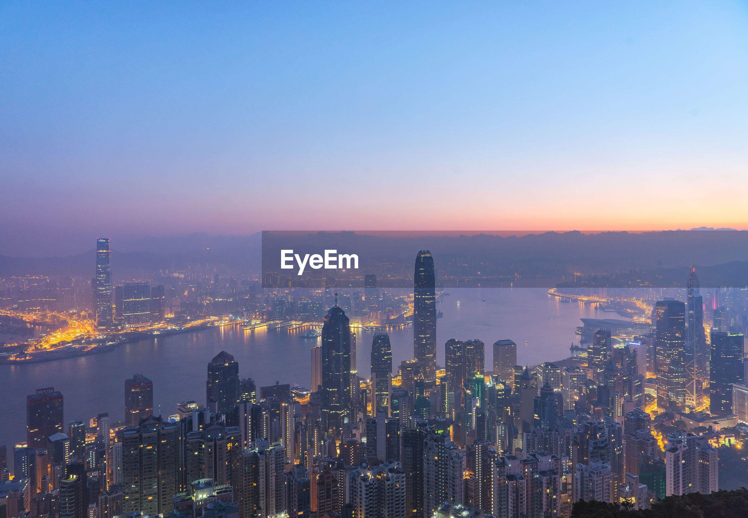 High angle view of river amidst illuminated city at dusk