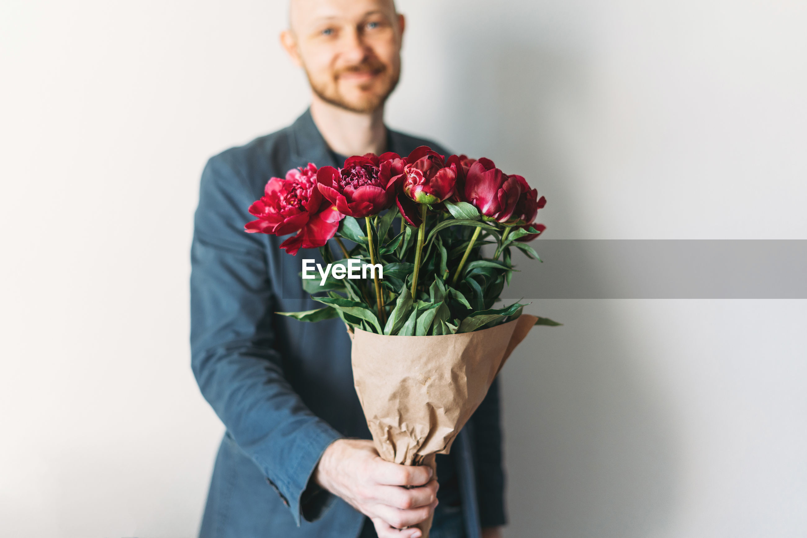 LOW SECTION OF MAN HOLDING ROSE AGAINST WHITE BACKGROUND