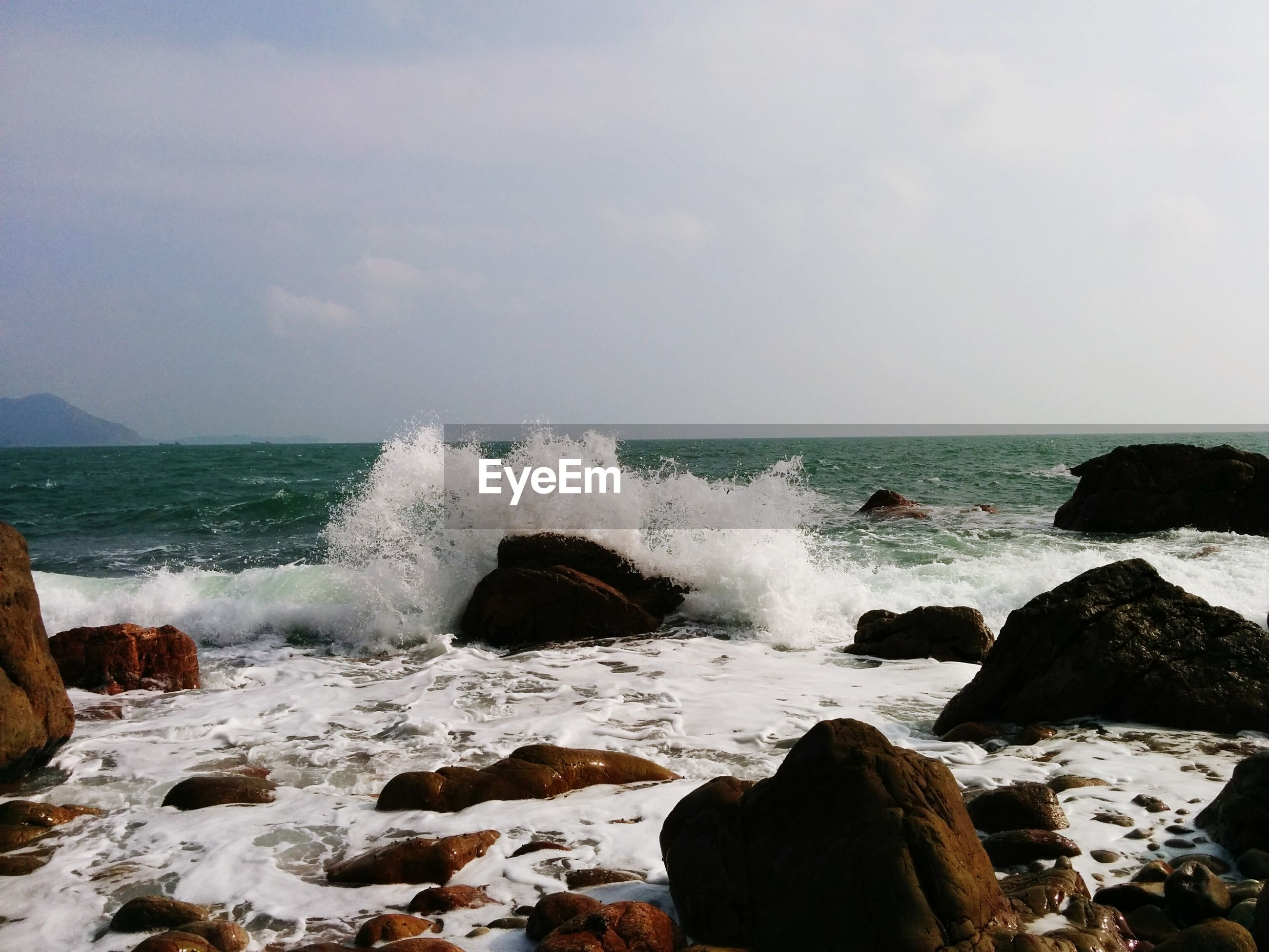 Waves splashing on rocks in sea against sky