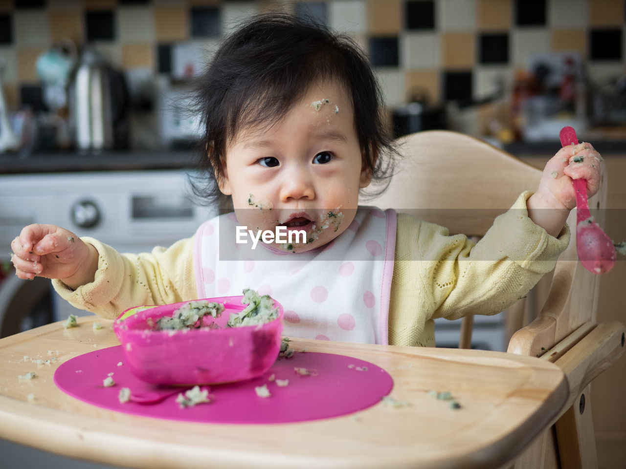 Portrait of cute girl with messy face having food at home