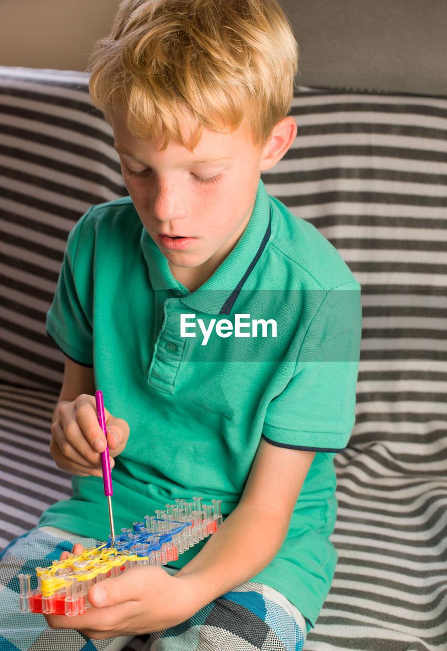 Boy making bracelet on loom while sitting on sofa