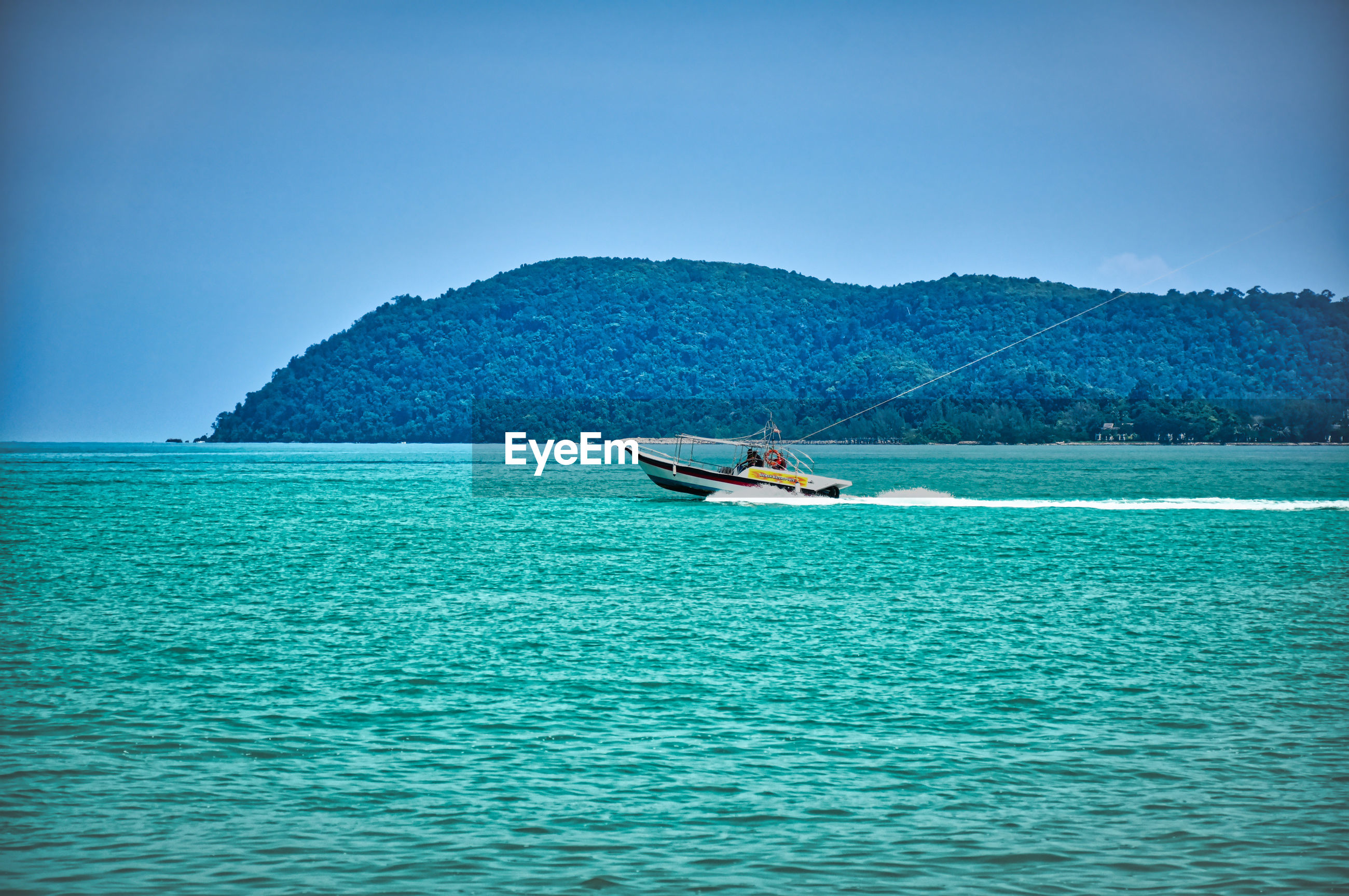 Speed boat on the waves of the azure andaman sea under the blue sky near the sandy beachshore
