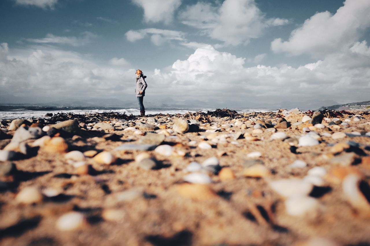 Surface level of woman standing on beach against sky