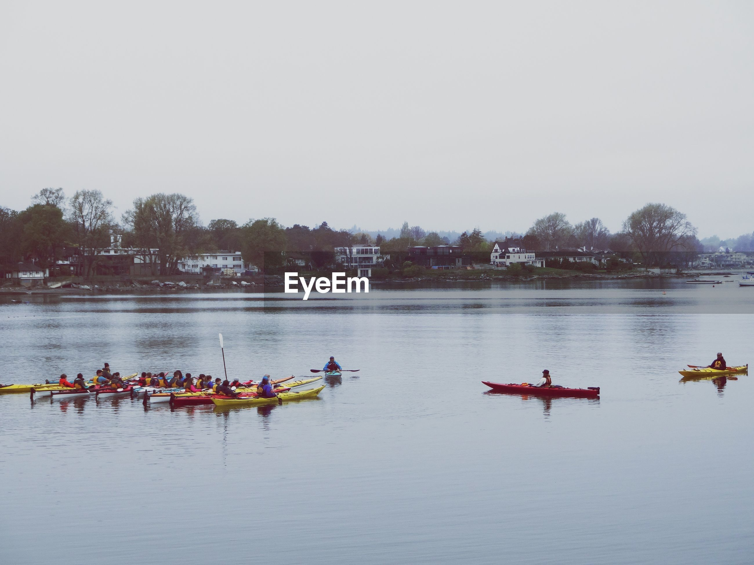 People boating on river against sky