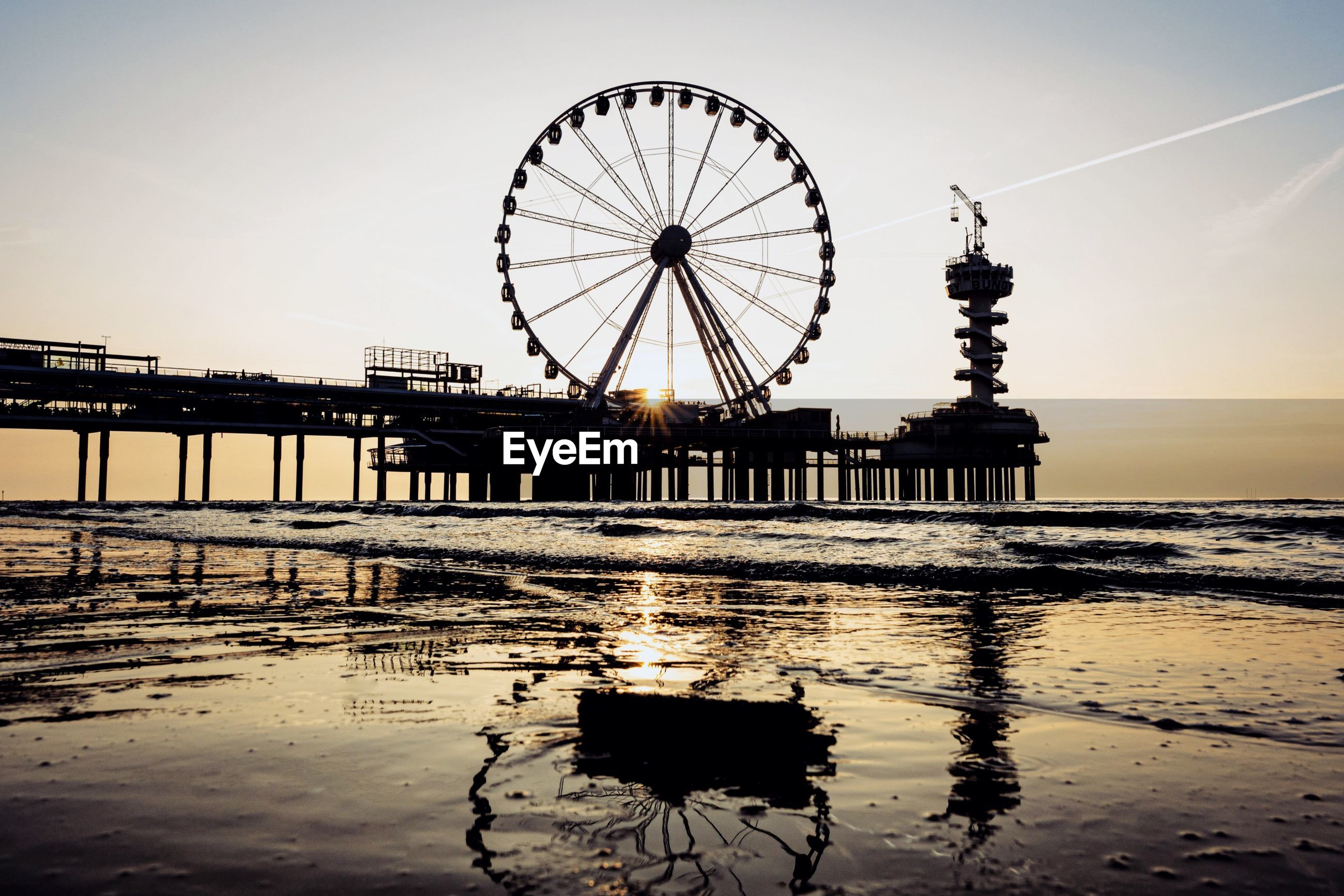 Silhouette of ferris wheel in sea at sunset