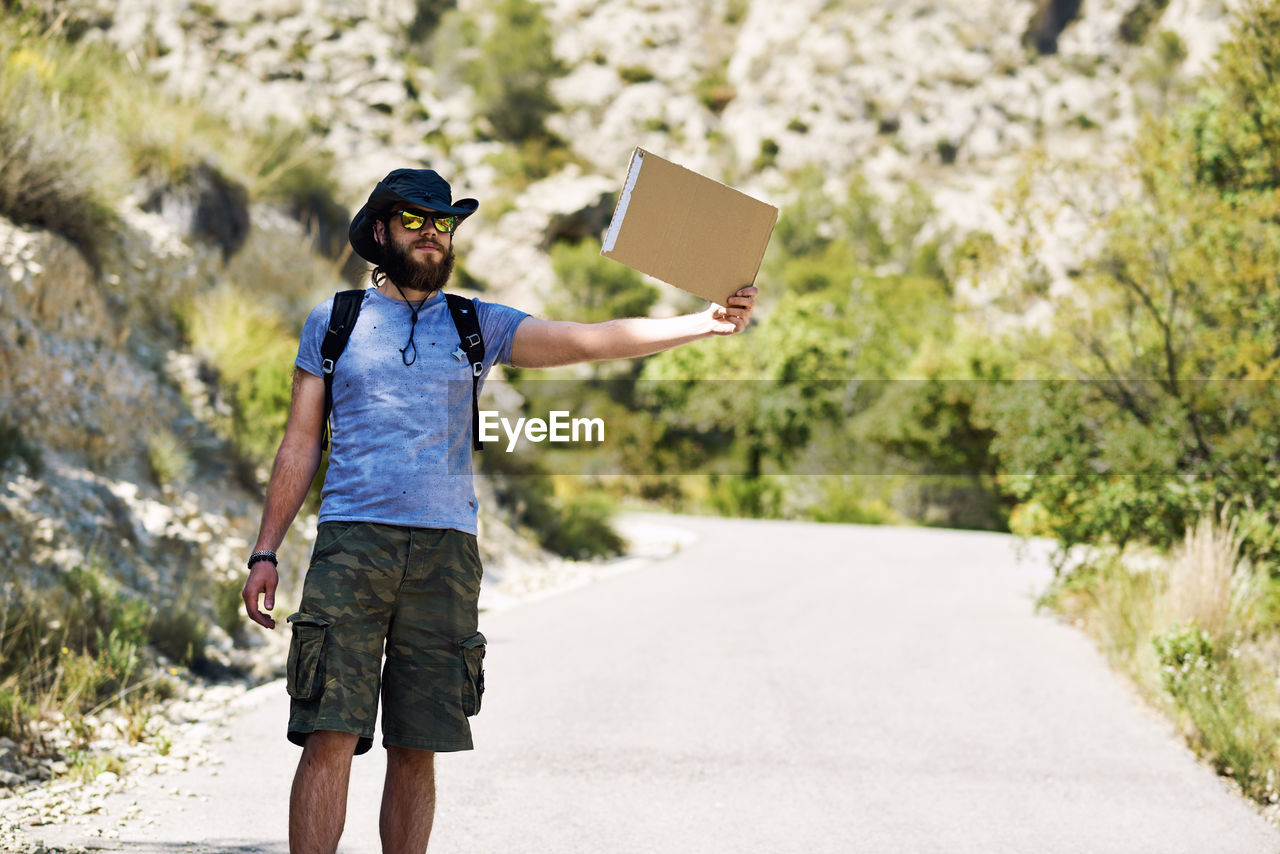 Man Hitchhiking On Country Road