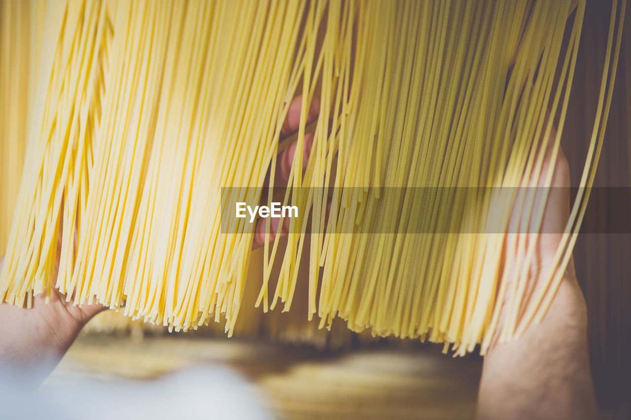 Cropped Image Of Hand Checking Spaghetti Drying In Factory