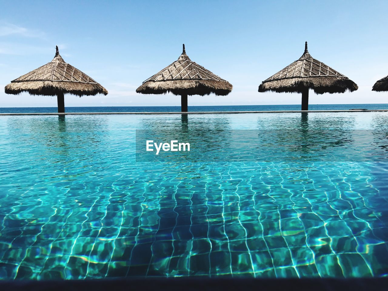 water, blue, swimming pool, sky, roof, pool, nature, thatched roof, clear sky, sea, beauty in nature, day, parasol, outdoors, tourist resort, holiday, relaxation, sunlight, waterfront, no people, turquoise colored