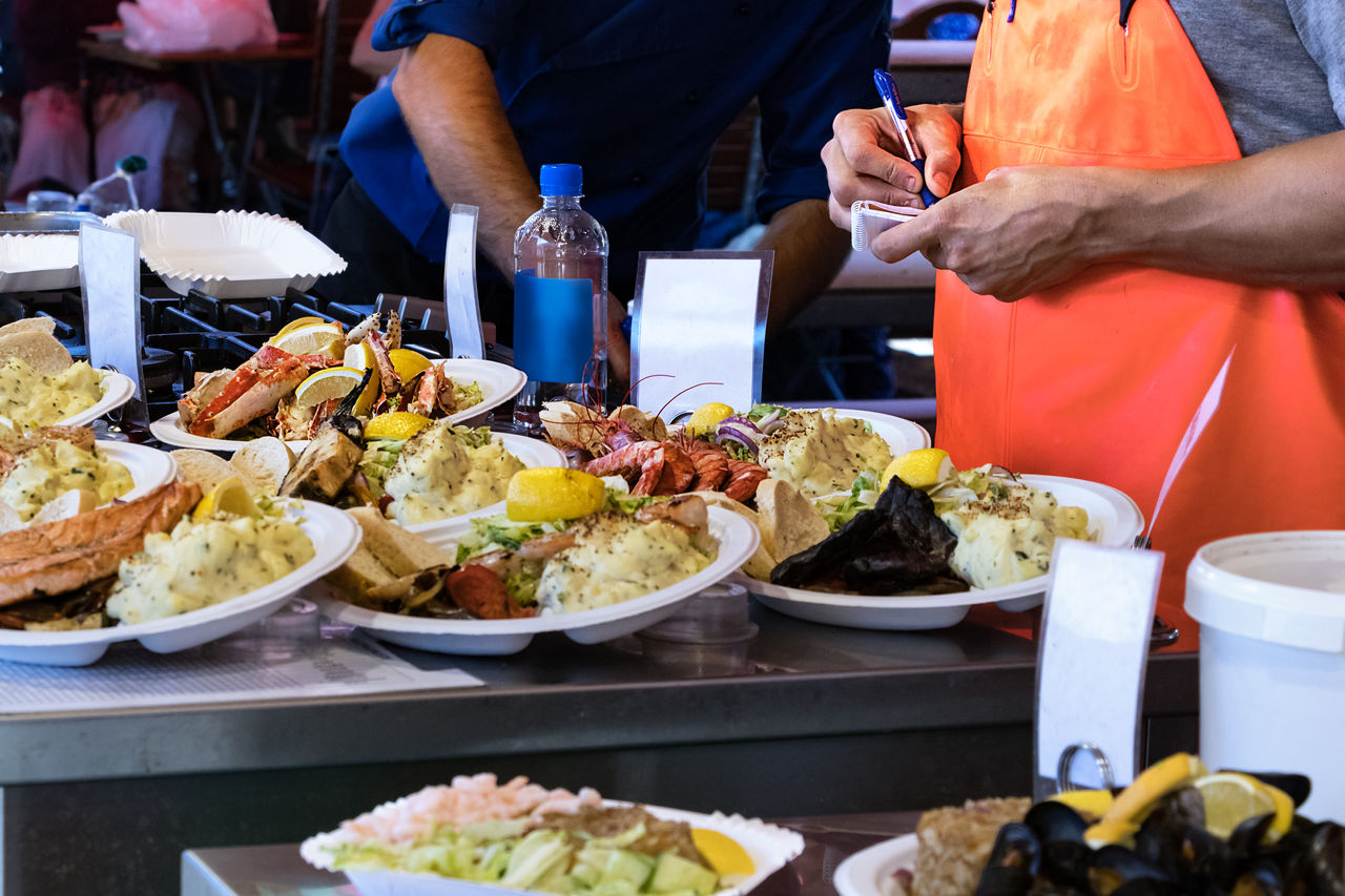food and drink, food, business, freshness, real people, midsection, ready-to-eat, plate, restaurant, table, incidental people, one person, indoors, healthy eating, serving size, wellbeing, meat, choice, men, hand, tray