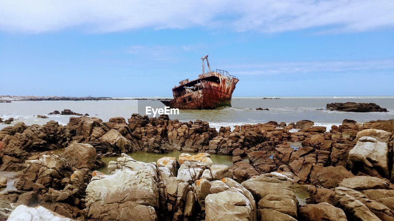 damaged, rock - object, sea, abandoned, water, obsolete, nature, run-down, sky, nautical vessel, day, bad condition, horizon over water, no people, beach, outdoors, crash, beauty in nature