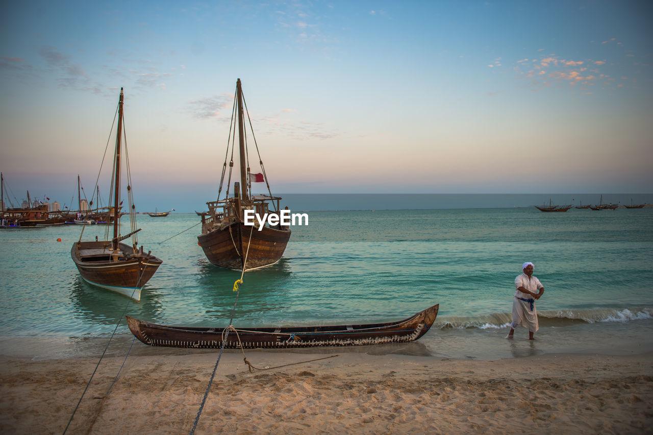 water, sea, nautical vessel, sky, mode of transportation, transportation, beauty in nature, scenics - nature, beach, land, real people, moored, sunset, nature, horizon, idyllic, horizon over water, lifestyles, men, outdoors, sailboat, fishing industry