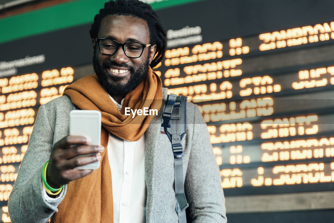 Smiling Man Using Mobile Phone While Standing Airport Departure Board