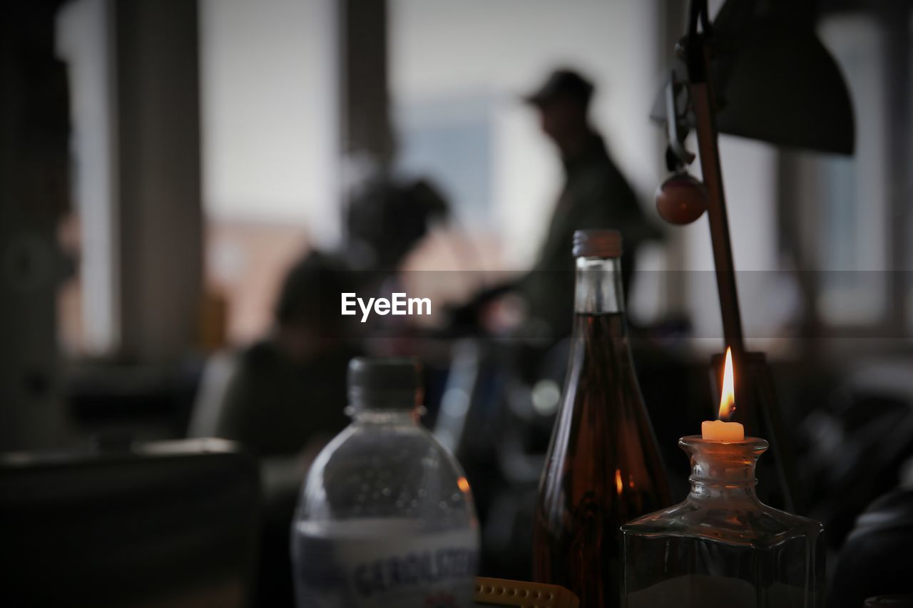 bottle, focus on foreground, indoors, close-up, real people, day