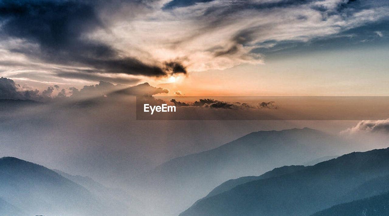 sky, beauty in nature, mountain, scenics - nature, cloud - sky, environment, tranquility, fog, landscape, nature, tranquil scene, mountain range, sunset, no people, sun, outdoors, sunlight, dramatic sky, non-urban scene, mountain peak