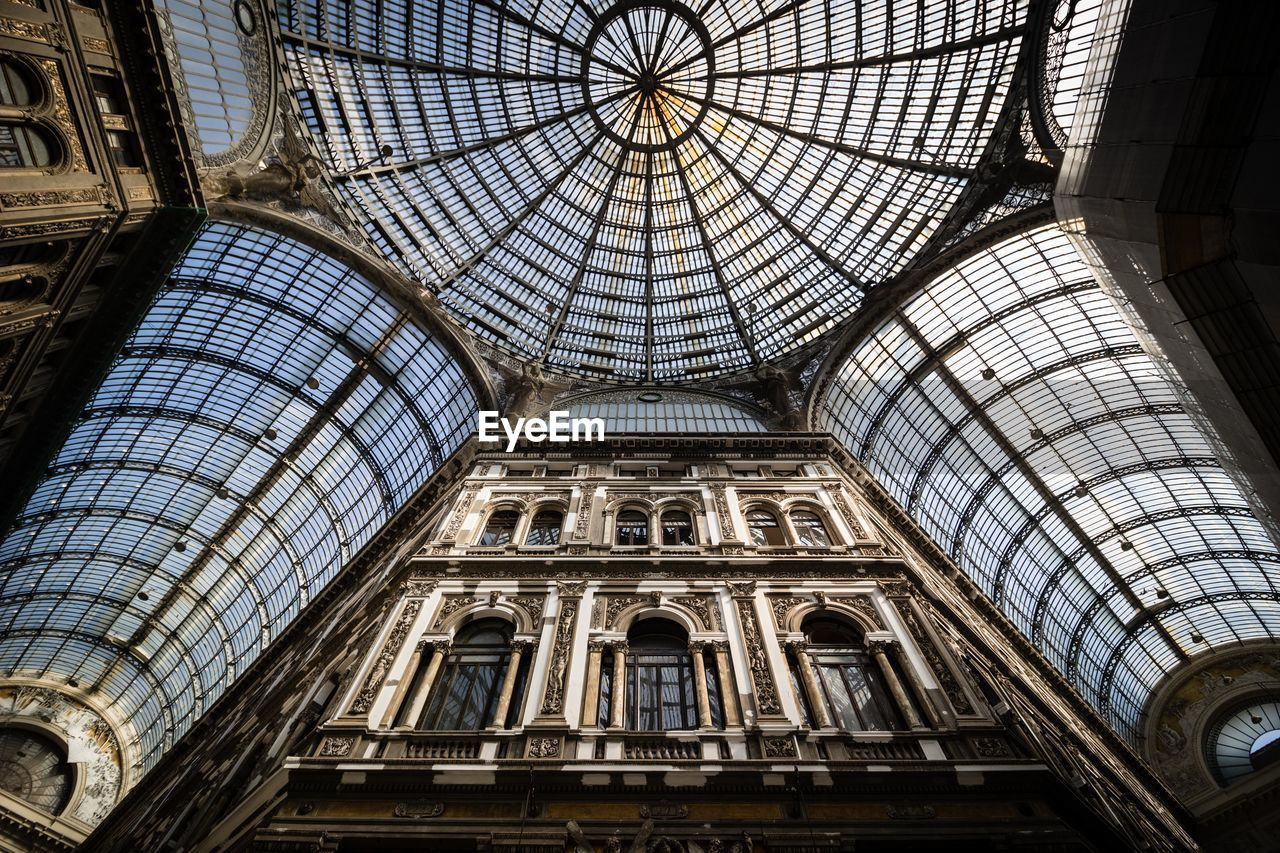 architecture, built structure, low angle view, ceiling, dome, indoors, no people, travel destinations, glass - material, architectural feature, tourism, pattern, day, architecture and art, history, city, the past, travel, arch, directly below, cupola, skylight, glass, ornate, gothic style