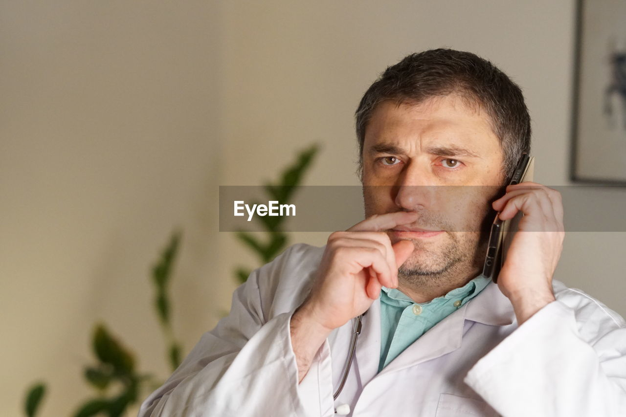 Portrait Of Mature Doctor Using Phone Against Wall