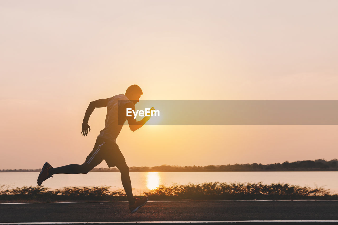 sunset, sky, water, lifestyles, real people, full length, beauty in nature, one person, orange color, leisure activity, scenics - nature, silhouette, nature, healthy lifestyle, exercising, tranquil scene, lake, non-urban scene, physical activity, leg