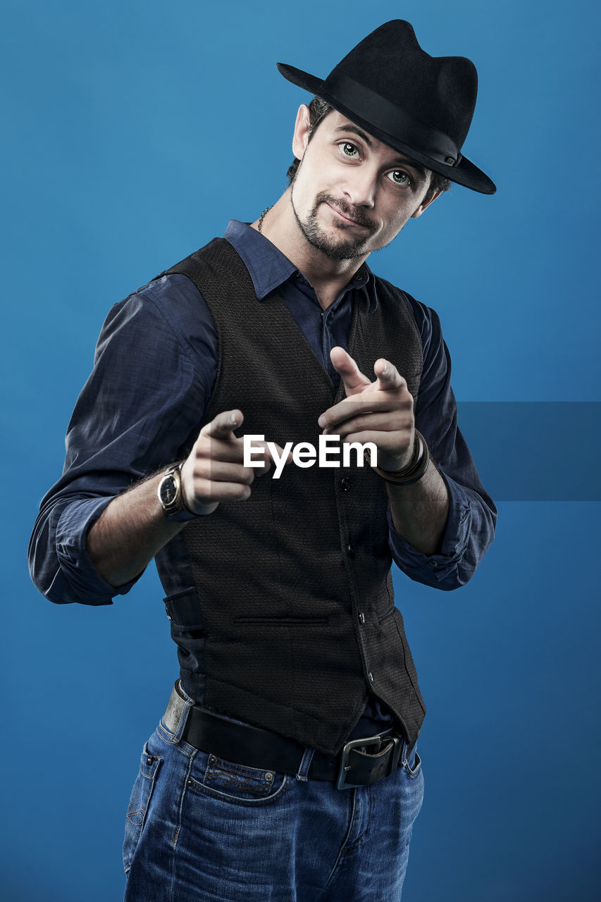 Portrait Of Fashionable Young Man Pointing At You While Standing Against Blue Background