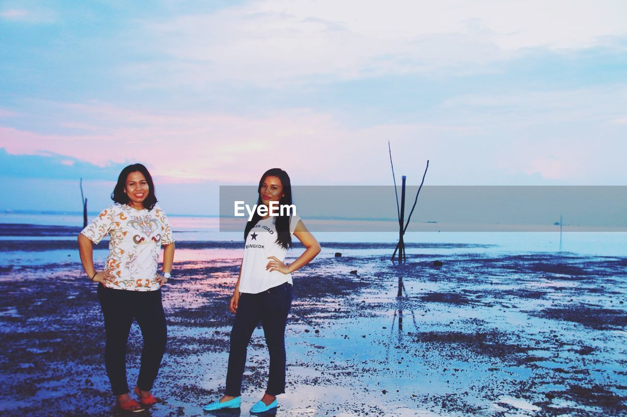 Portrait of female friends standing at beach against sky during sunset