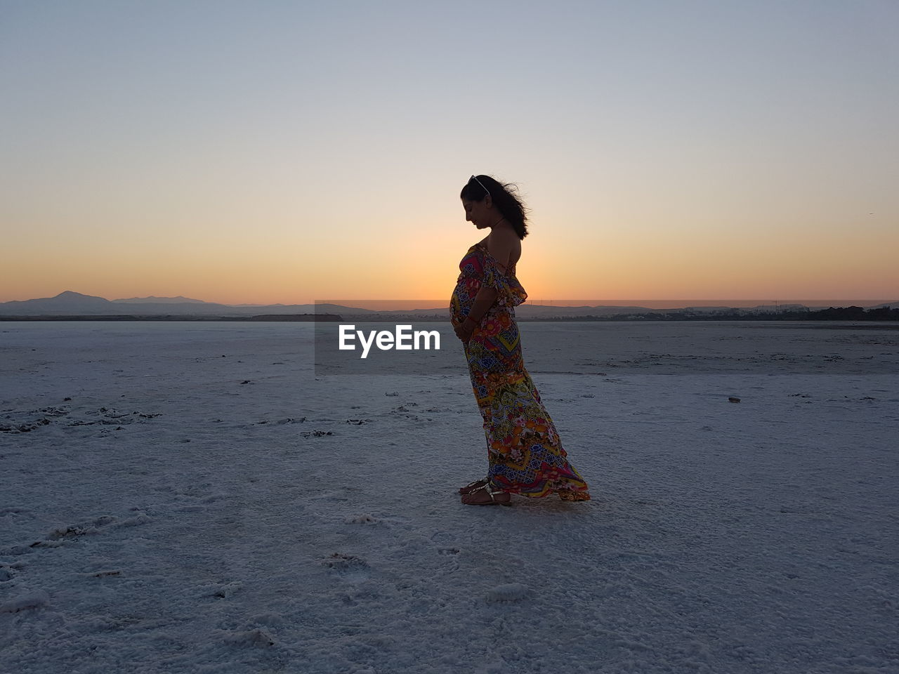 Side view of pregnant woman standing at salt flat against sky