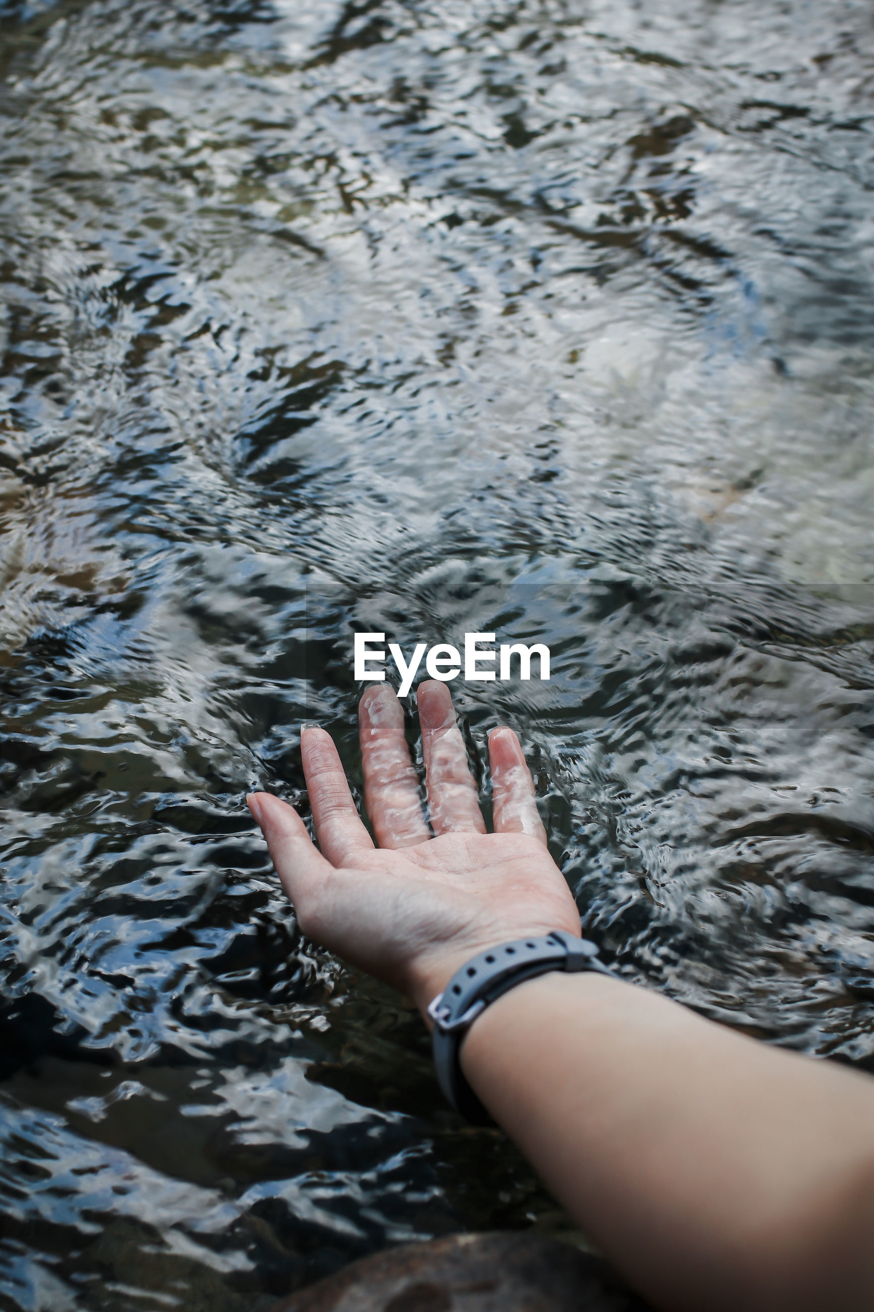 Cropped hand of woman touching river water