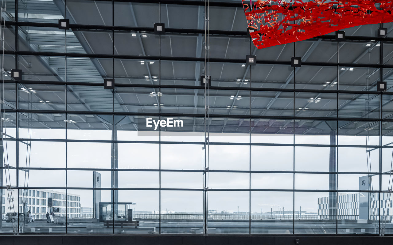 LOW ANGLE VIEW OF GLASS WINDOW IN AIRPORT BUILDING