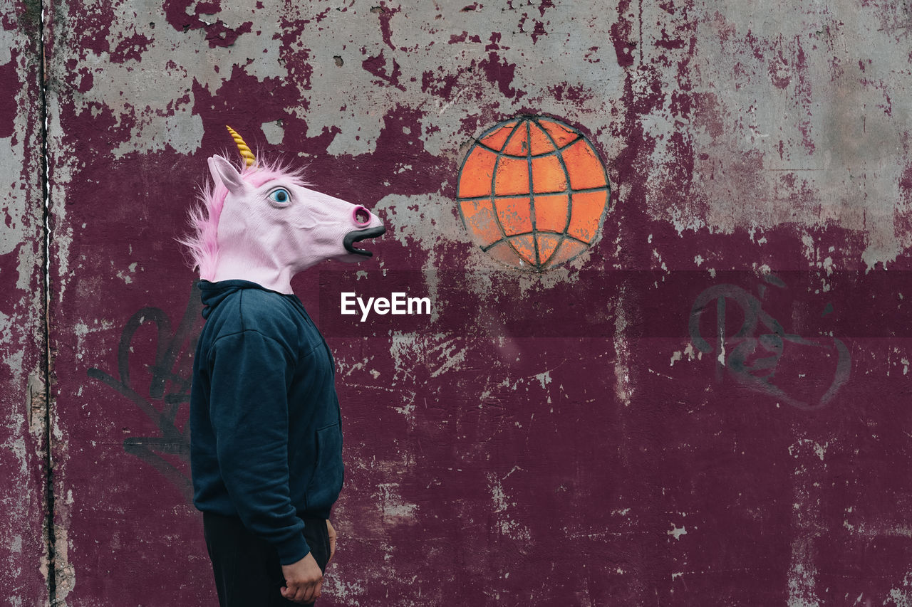 Side View Of Man Wearing Horse Mask While Standing Against Wall
