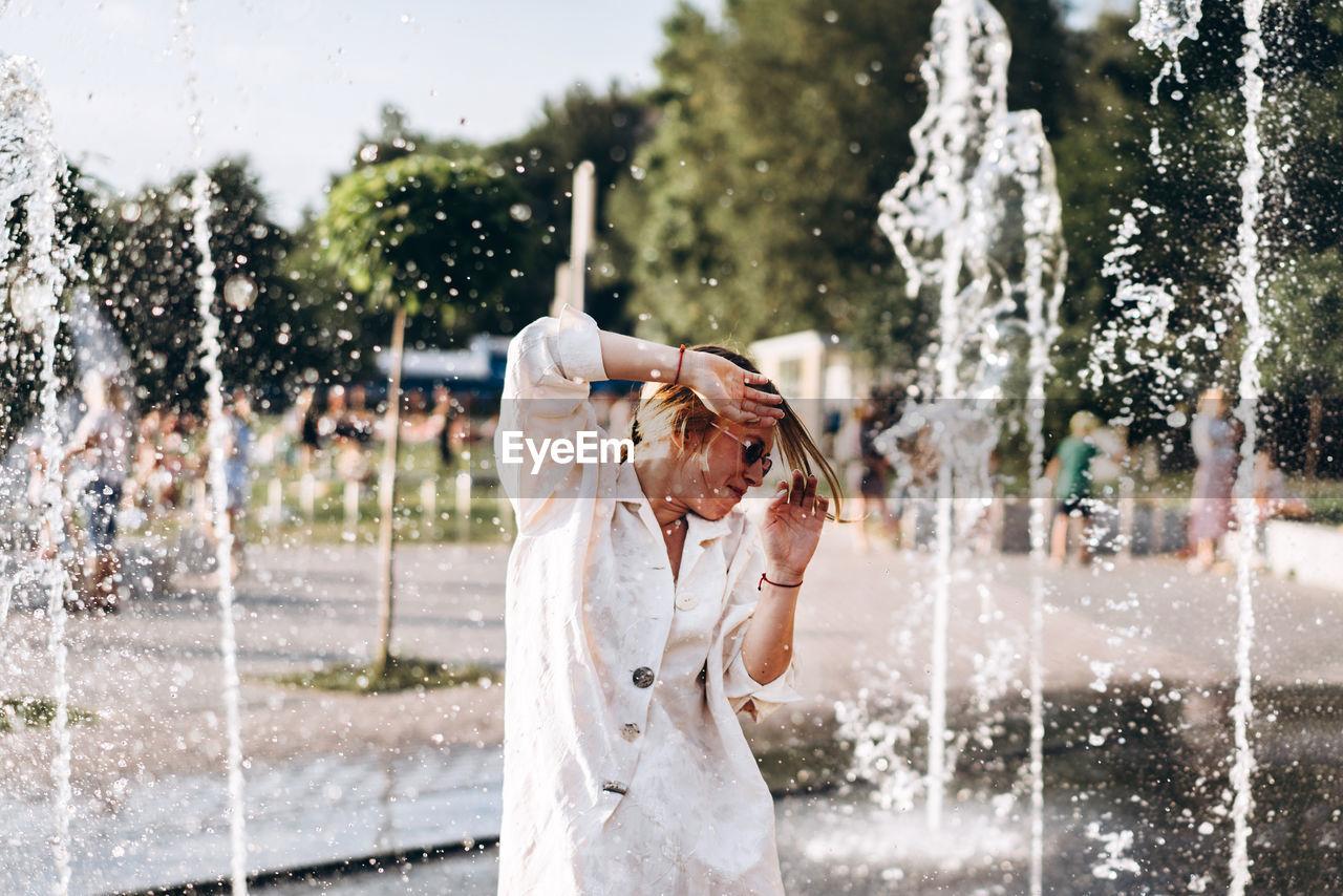 Young Woman Enjoying At Water Fountain