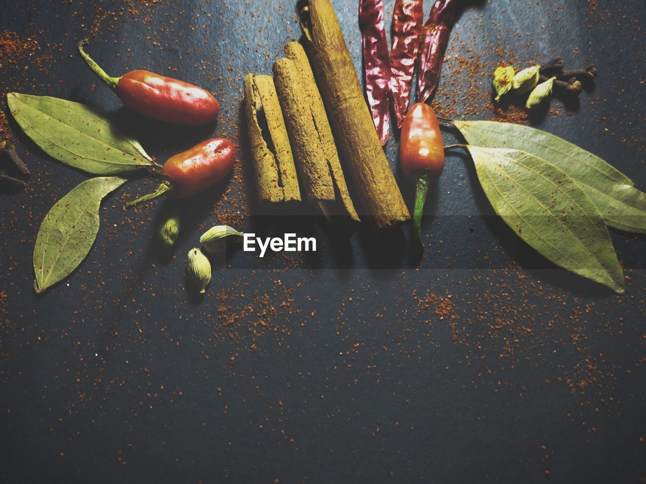 Bay leaves, cinnamon and chili at black background