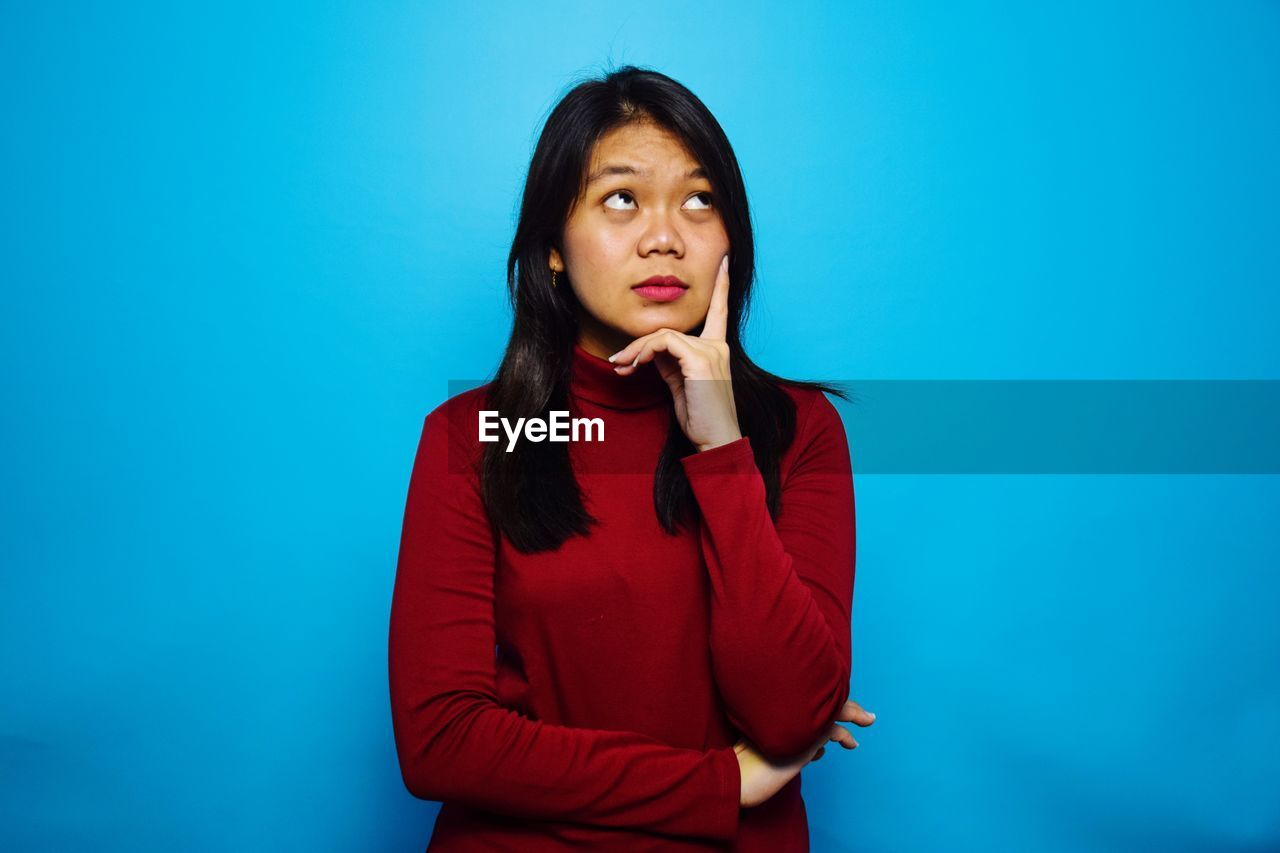 PORTRAIT OF A YOUNG WOMAN AGAINST BLUE BACKGROUND