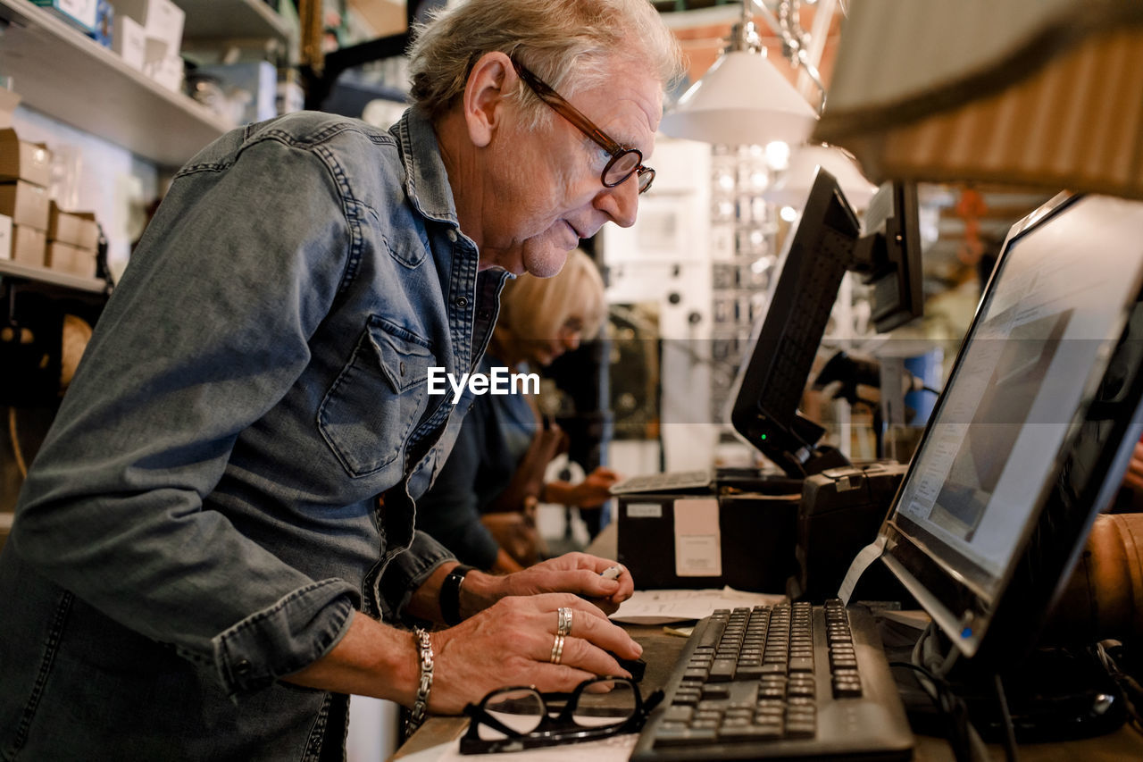 SIDE VIEW OF A MAN WORKING WITH LAPTOP IN OFFICE