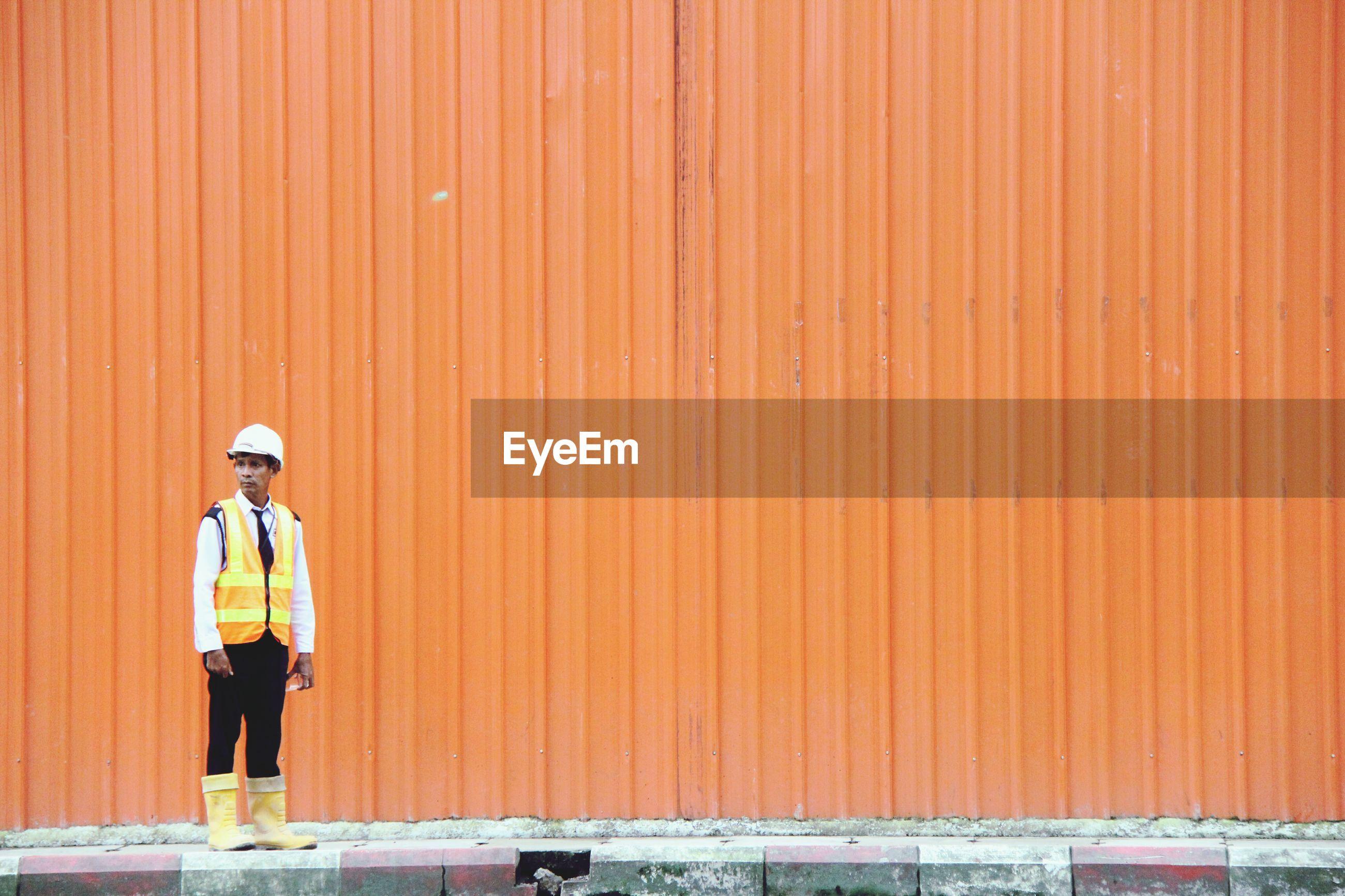 Manual worker wearing reflective clothing and hardhat standing against orange corrugated iron