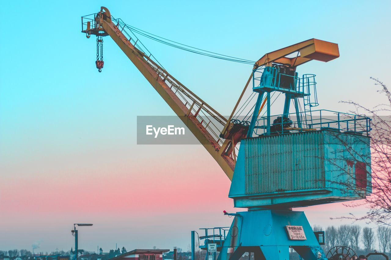 crane - construction machinery, industry, crane, freight transportation, construction site, low angle view, construction machinery, machinery, transportation, outdoors, shipping, no people, industrial equipment, built structure, day, sky, cargo container, sunset, clear sky, architecture, shipyard