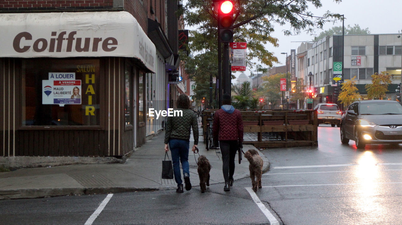 PEOPLE WALKING WITH DOG ON STREET IN CITY