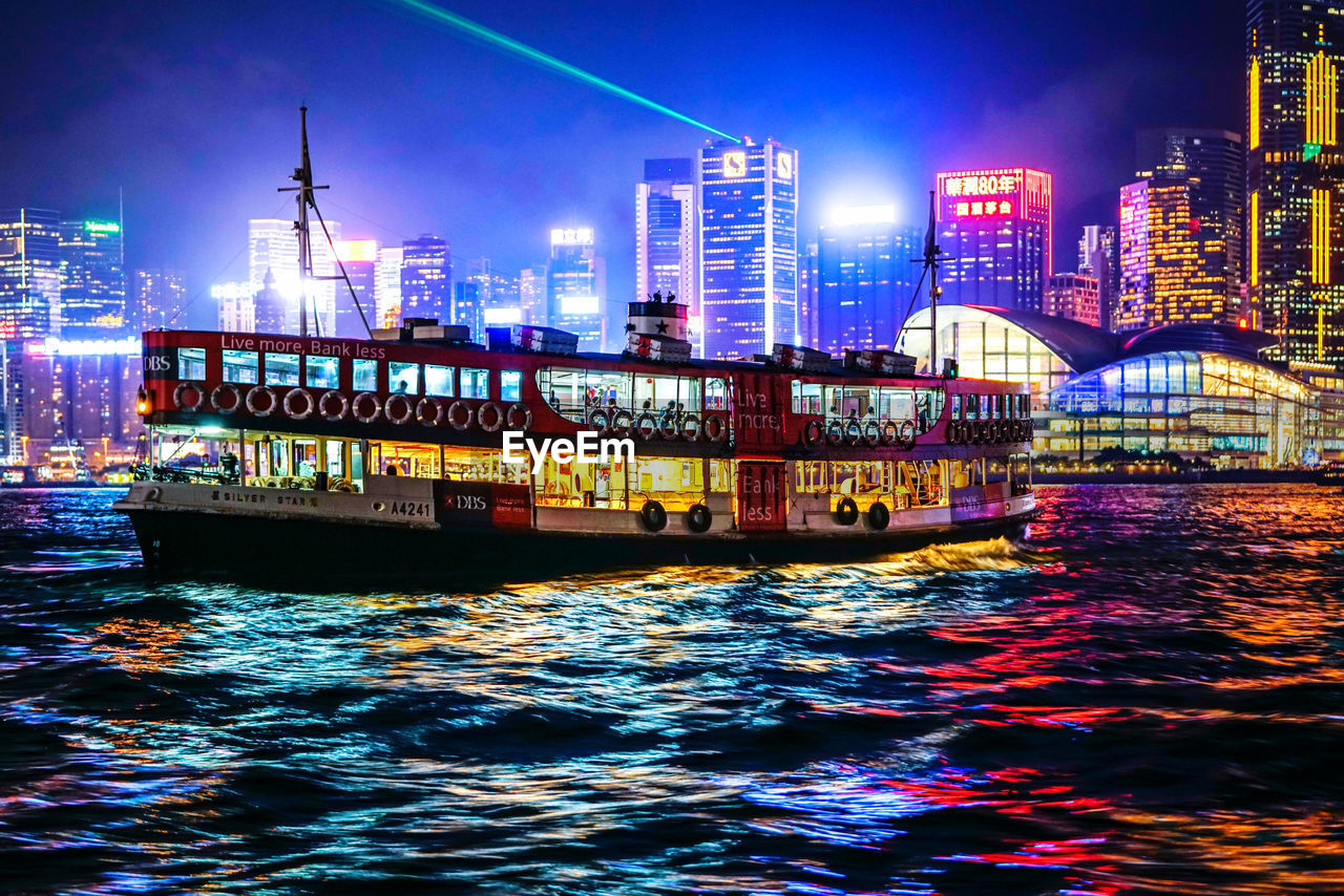 water, architecture, built structure, building exterior, waterfront, illuminated, city, nautical vessel, transportation, night, sky, river, no people, mode of transportation, nature, building, outdoors, multi colored, office building exterior, skyscraper