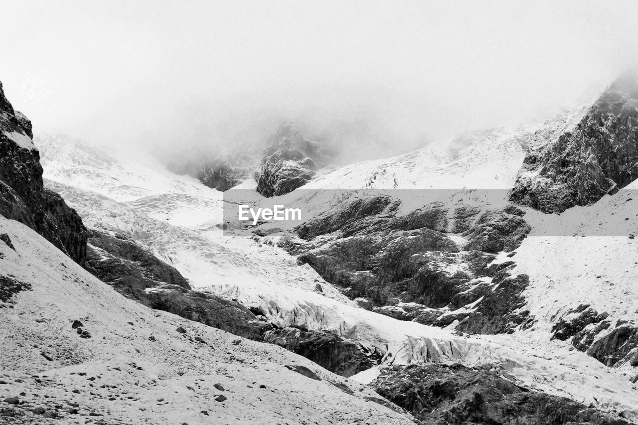 mountain, beauty in nature, environment, landscape, scenics - nature, cold temperature, snow, tranquility, nature, day, tranquil scene, no people, fog, winter, non-urban scene, mountain range, sky, mountain peak, remote, outdoors, snowcapped mountain