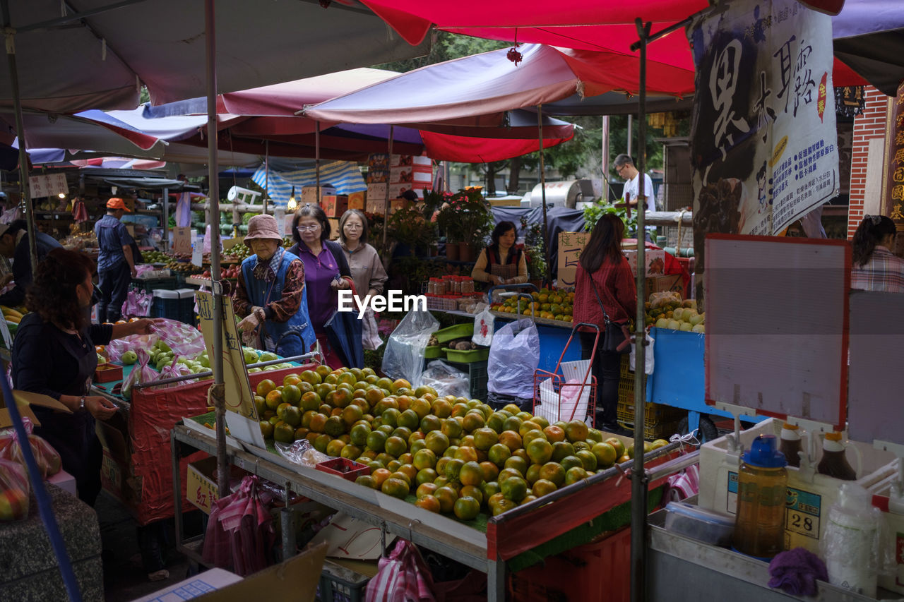 market, food, food and drink, market stall, retail, healthy eating, choice, group of people, freshness, real people, variation, business, wellbeing, small business, women, men, vegetable, people, fruit, selling, buying, retail display, street market, consumerism, sale, outdoors
