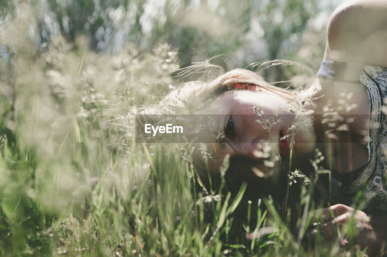 Close-Up Of A Young Woman Lying In Grass