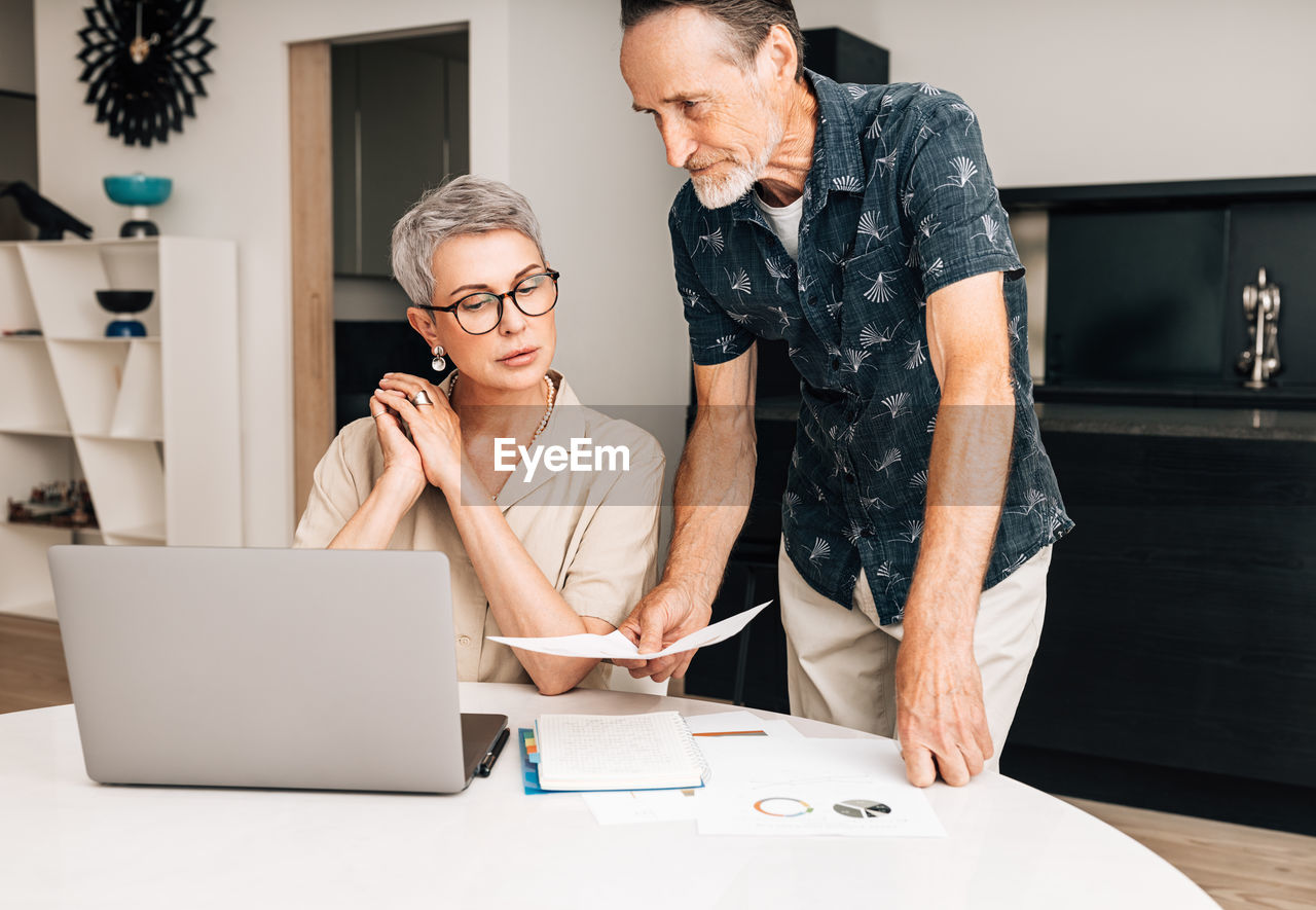 Senior couple working on laptop at home
