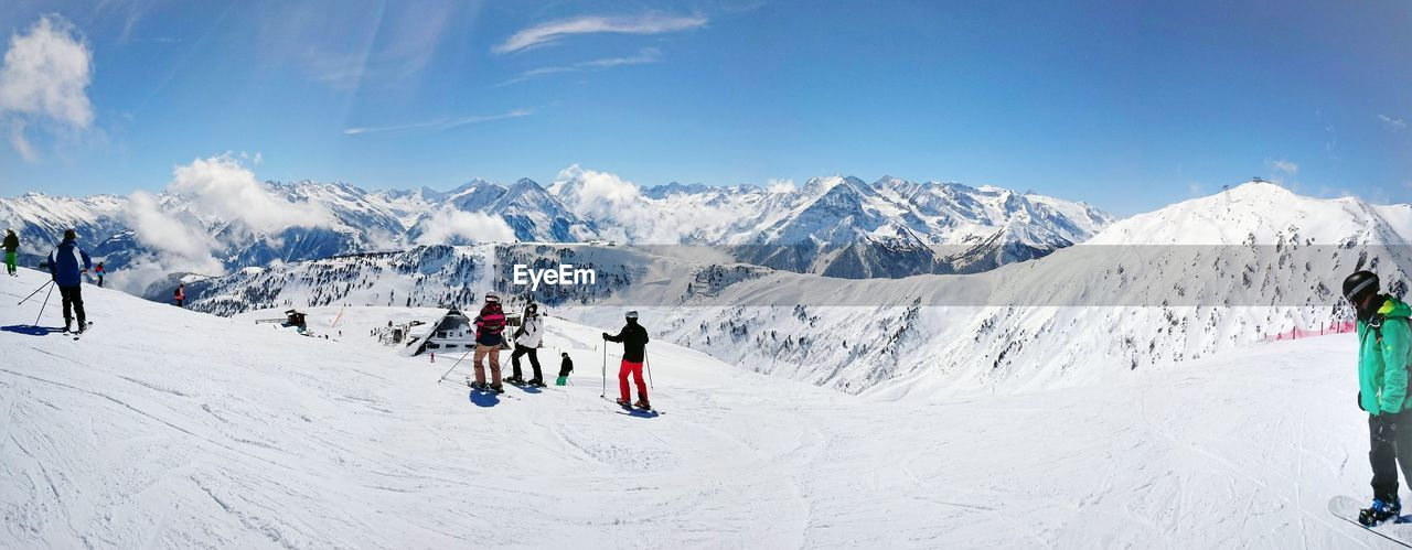 snow, cold temperature, group of people, leisure activity, winter, mountain, sport, real people, sky, mountain range, lifestyles, adventure, scenics - nature, winter sport, beauty in nature, nature, day, holiday, skiing, snowcapped mountain, outdoors