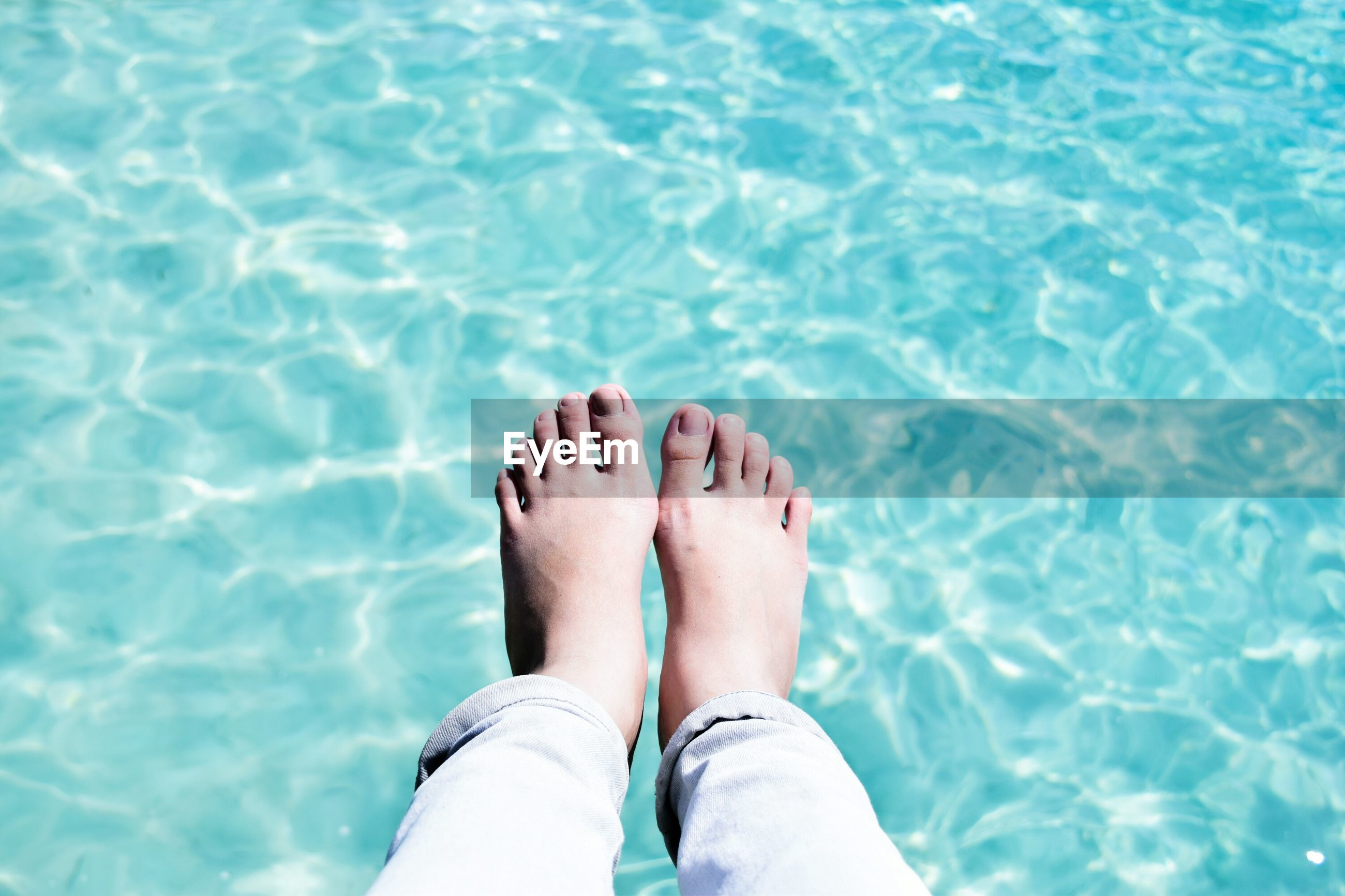 Low section of woman relaxing against swimming pool