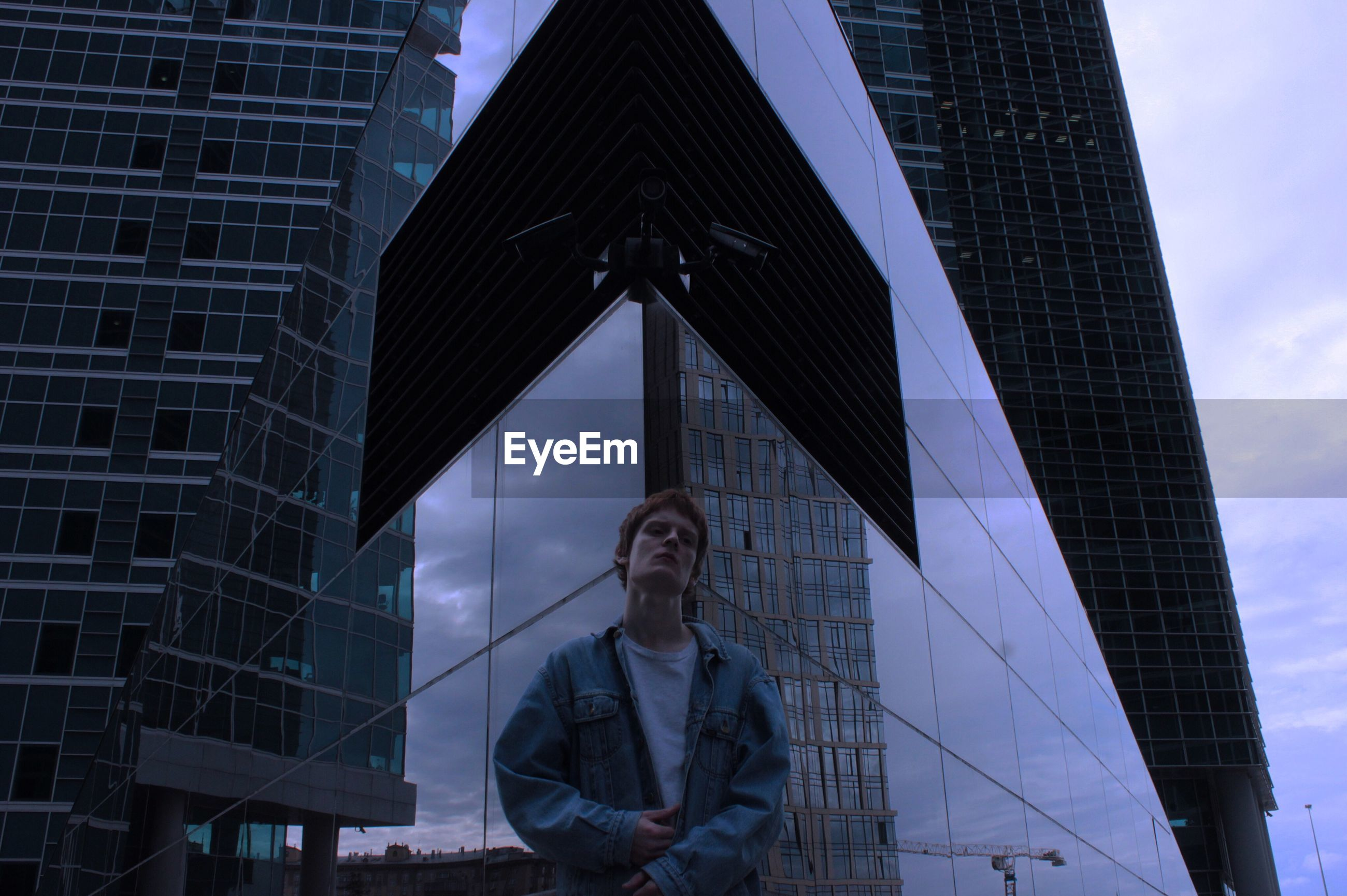 Low angle view of man standing against modern buildings