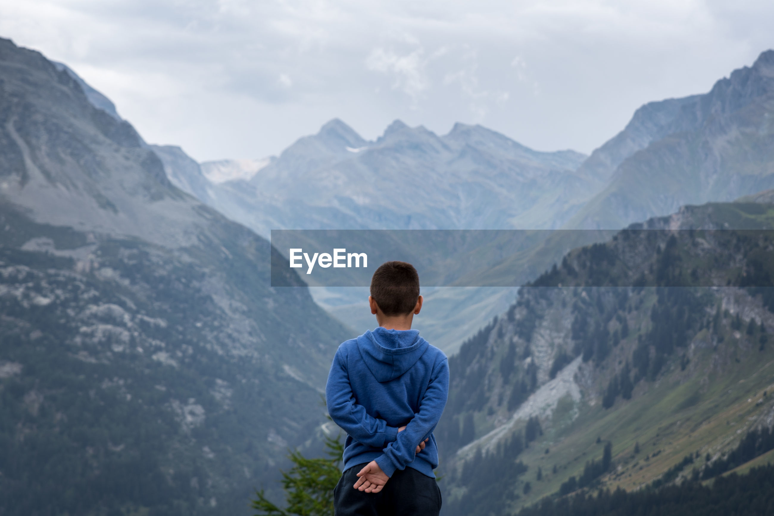 Rear view of boy looking at mountain range