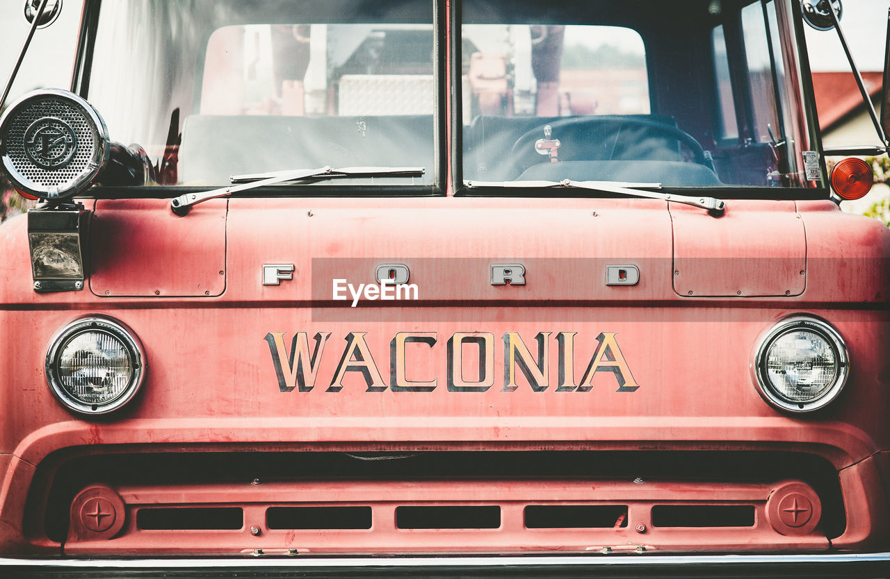 CLOSE-UP OF RED VINTAGE CAR ON BUS