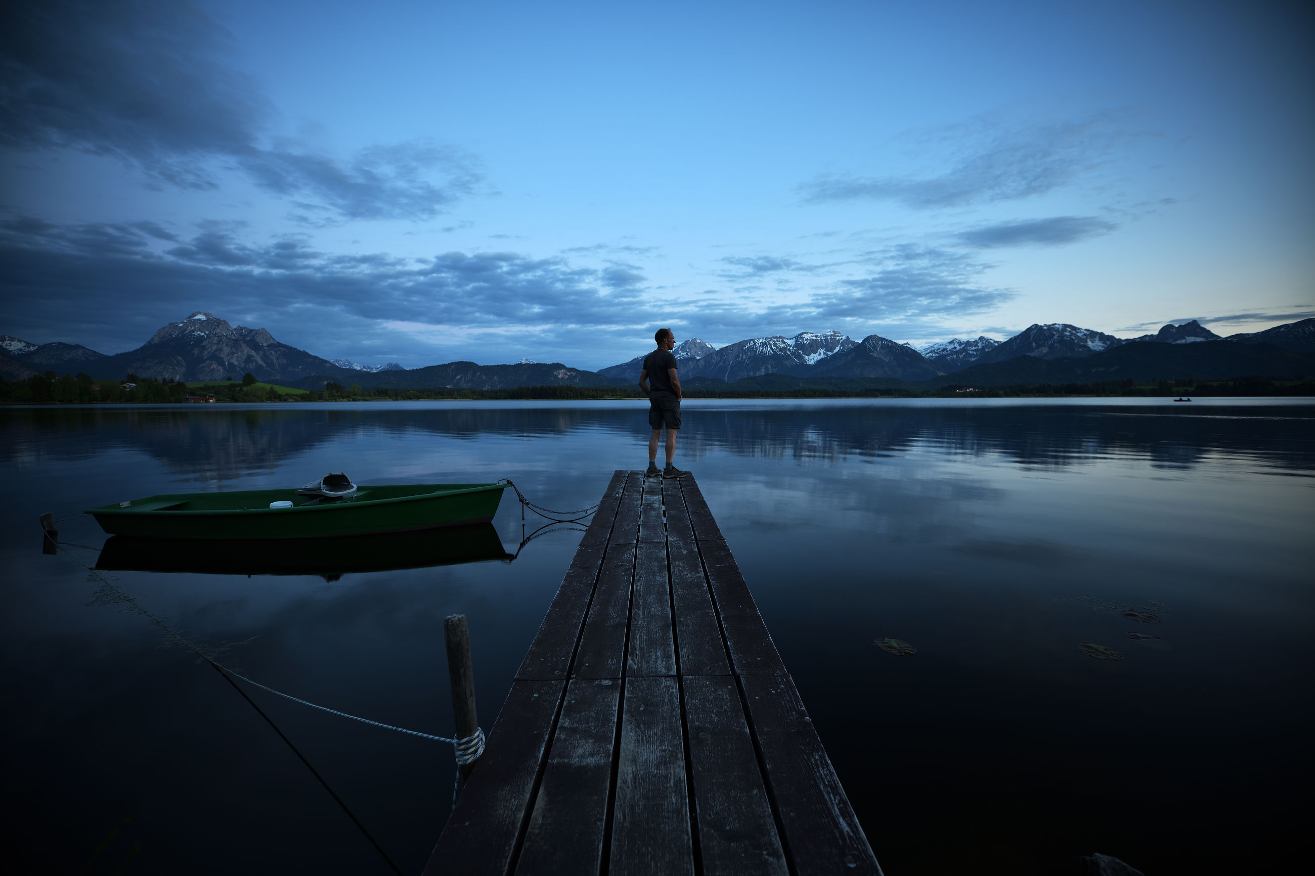 Man standing on pier over lake against sky