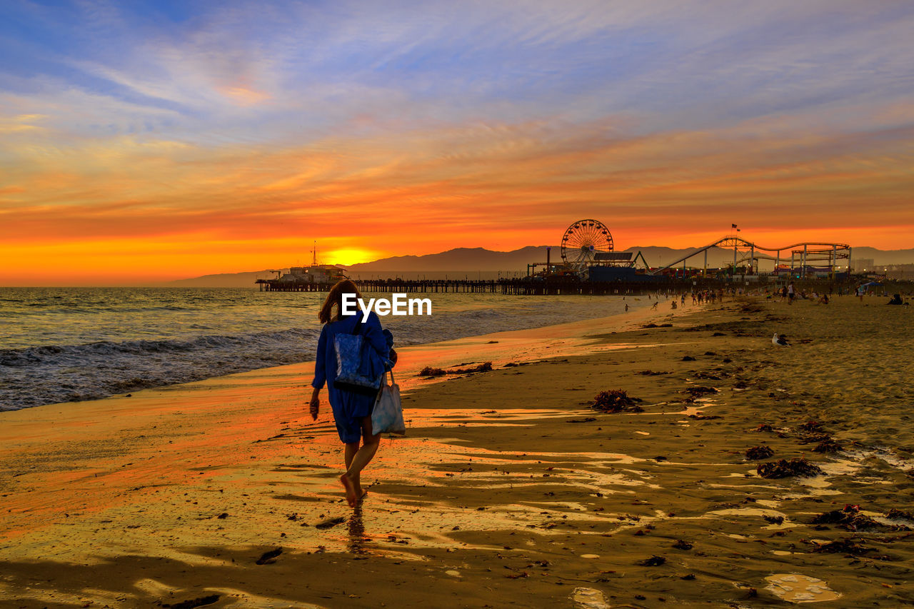sunset, sky, land, water, real people, beach, sea, cloud - sky, beauty in nature, orange color, scenics - nature, lifestyles, leisure activity, full length, rear view, nature, sand, women, people, outdoors
