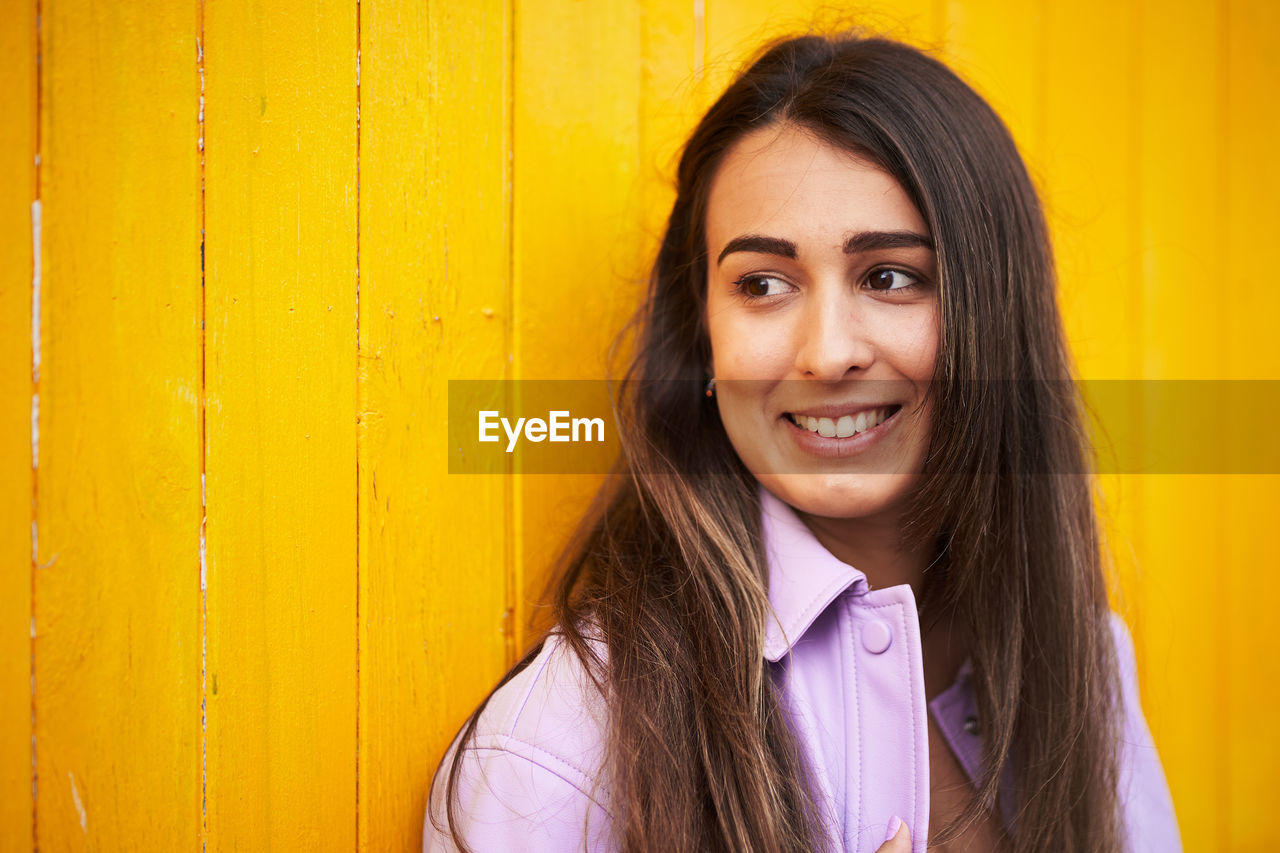 PORTRAIT OF A SMILING YOUNG WOMAN AGAINST YELLOW WALL